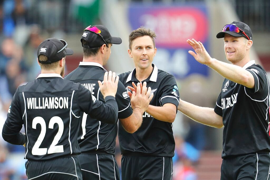 New Zealand's Trent Boult, without cap, celebrates with teammates after dismissing India's Ravindra Jadeja during the Cricket World Cup semifinal match.