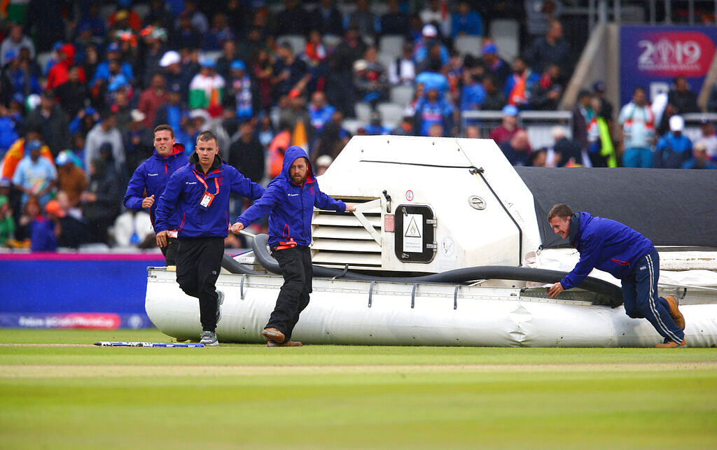Groundsmen bring out a water removal machine as it rains during the Cricket World Cup semifinal match between India and New Zealand at Old Trafford in Manchester.