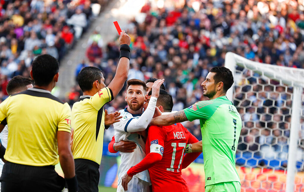 Argentina's Lionel Messi, center left, and Chile's Gary Medel, center right, scuffle as referee Mario Diaz, from Paraguay shows the red card to both of them during the Copa America third-place soccer match