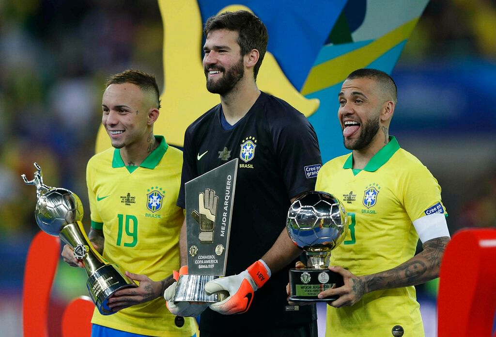 Brazil's Everton, left, holds his Top Scorer trophy as he poses with teammates goalkeeper Alisson holding his Best Goalkeeper trophy and Brazil's Dani Alves holding his top scorer trophy.