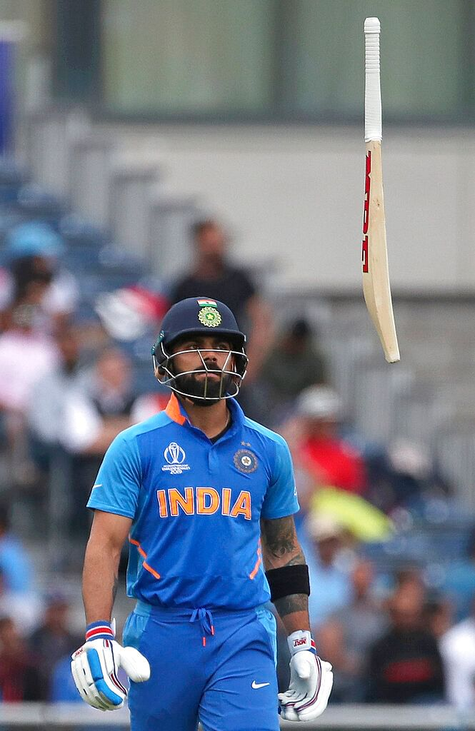 India's captain Virat Kohli throws his bat in frustration after being dismissed by New Zealand's Trent Boult.