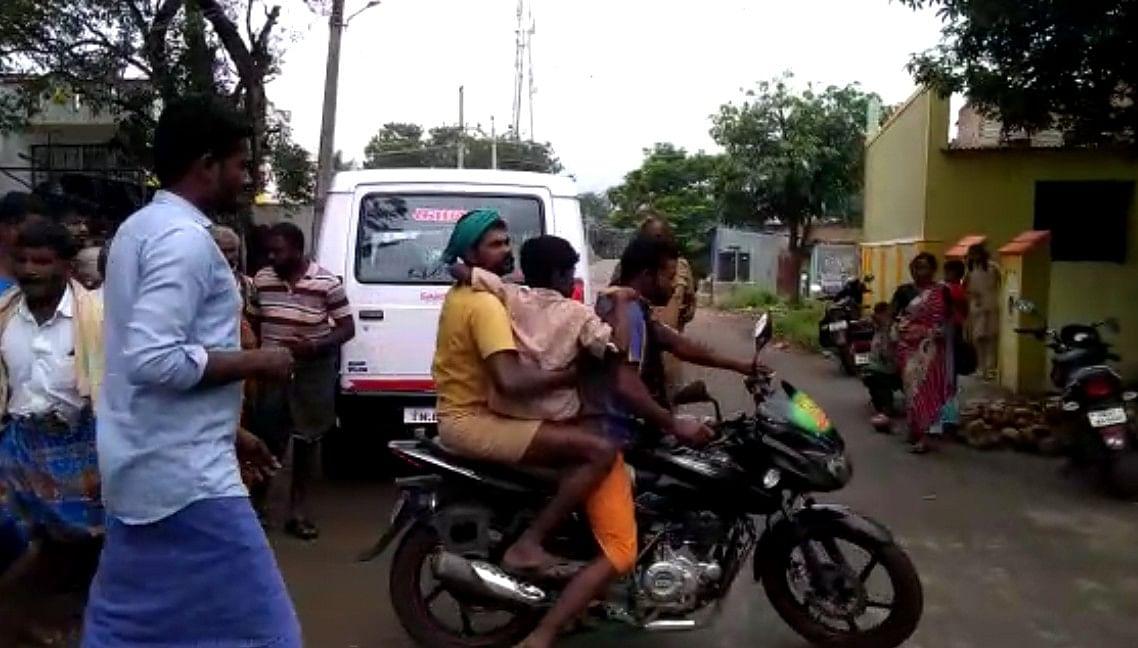 காயம்பட்ட மாணவனைத் தூக்கிச் செல்லும் கிராமத்தினர்