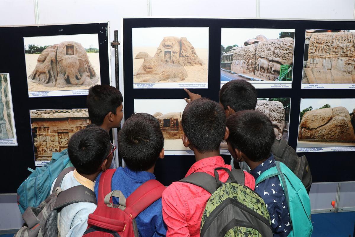 மகாபலிபுரத்திலுள்ள கலை நயம்மிக்க சிற்பங்களின் படங்களைப் பார்வையிடும் சிறுவர்கள்