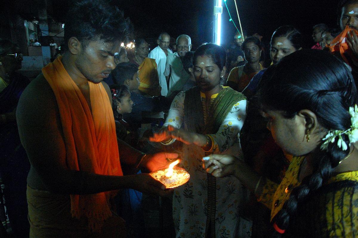 காவடியை பூஜித்து மக்களுக்கு சேவிக்கும் பக்தர்.