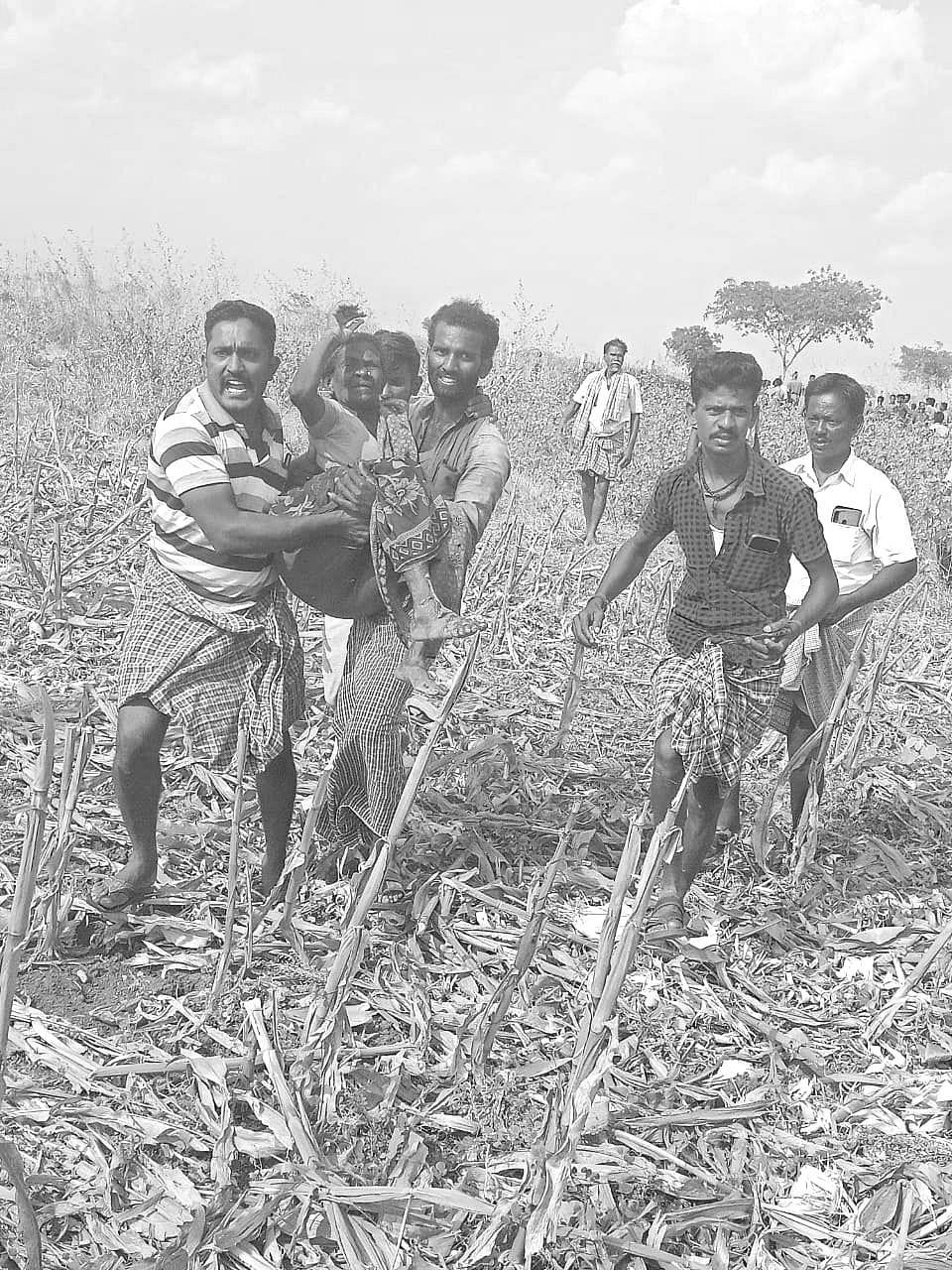 காயம்பட்டவரை தூக்கிச் செல்லும் ஊர்மக்கள்