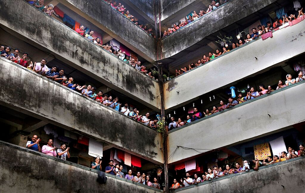 People clap from balconies in show of appreciation to health care workers at a Chawl in Mumbai, India