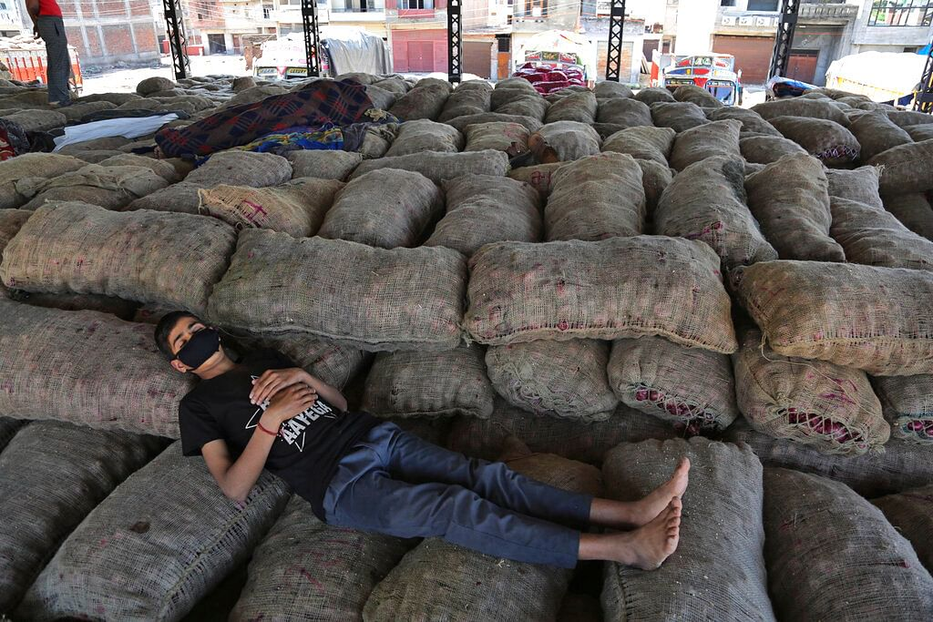 An Indian laborer sleeps on sacks of onions at a market during lockdown in Jammu, India.