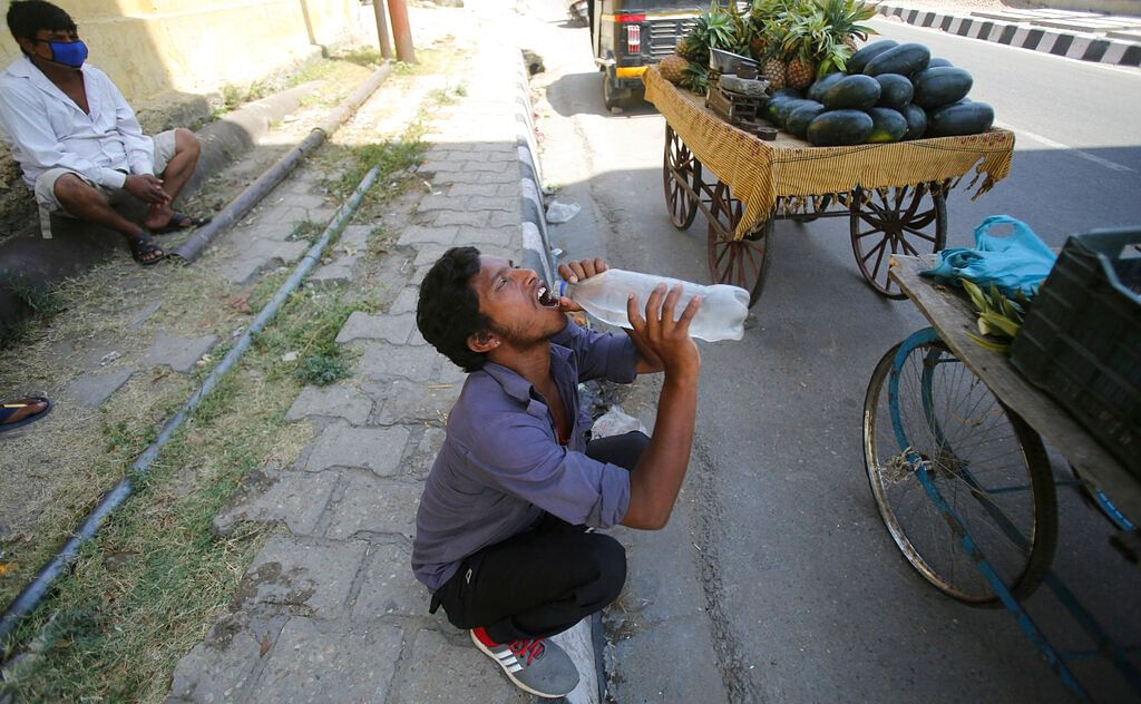 A vendor drinks water on a summer day in Jammu, India.