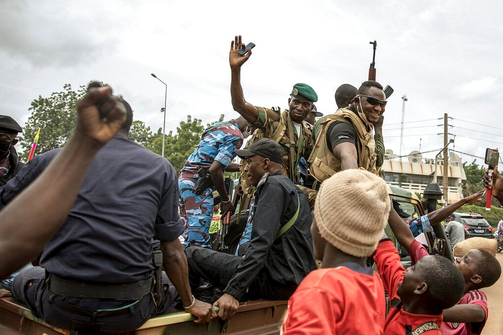 People cheer in celebration as security forces drive through the streets of the capital Bamako, Mali, Wednesday, Aug. 19, 2020