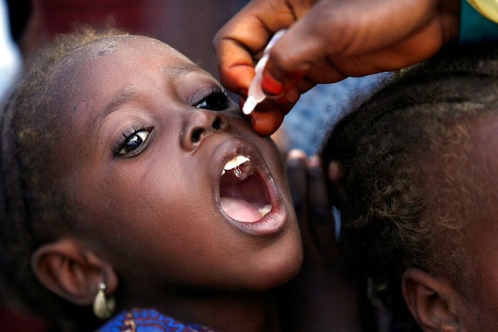 In this Sunday, Aug. 28, 2016 file photo, a health official administers a polio vaccine to a child at a camp for people displaced by Islamist Extremists, in Maiduguri, Nigeria. Health authorities on Tuesday, Aug. 25, 2020 are expected to declare the African continent free of the wild poliovirus after decades of effort, though cases of vaccine-derived polio are still sparking outbreaks of the paralyzing disease in more than a dozen countries.