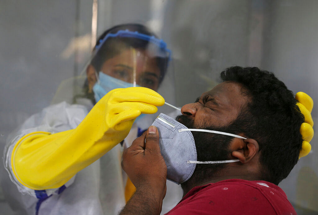 A health worker takes a nasal swab sample to test for COVID-19 in Hyderabad, India