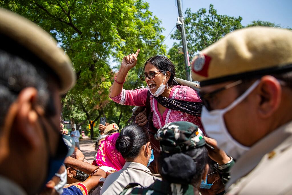 An Indian activist shouts slogans as she is detained by police during a protest in New Delhi, India
