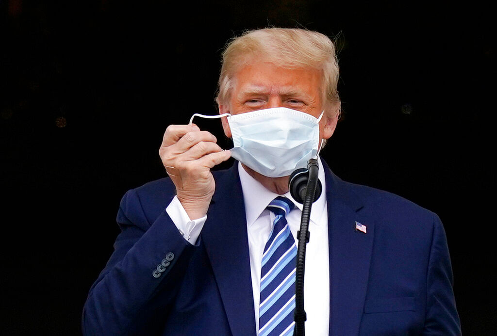 US President Donald Trump removes his face mask to speak from the Blue Room Balcony of the White House to a crowd of supporters