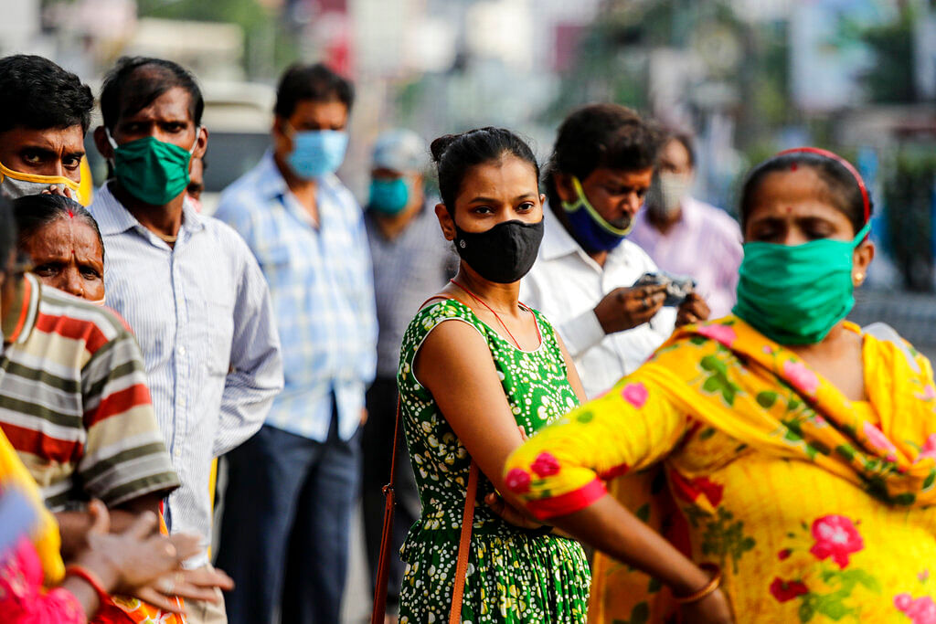 Commuters with face mask to prevent the spread of the coronavirus wait for a bus in Kolkata, India