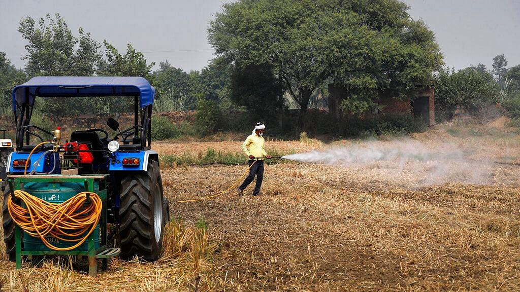 A farmer sprays bio-decomposer