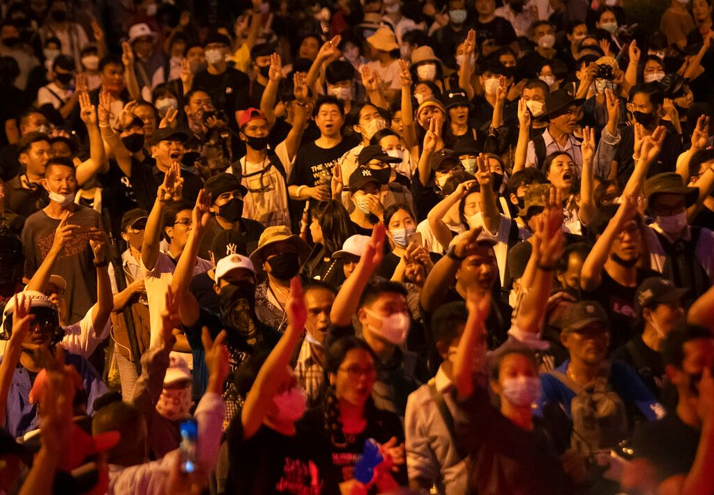 Pro-democracy protesters raise a three-finger salute, a sign of resistance, as they gather outside the Government House during a rally in Bangkok, Thailand