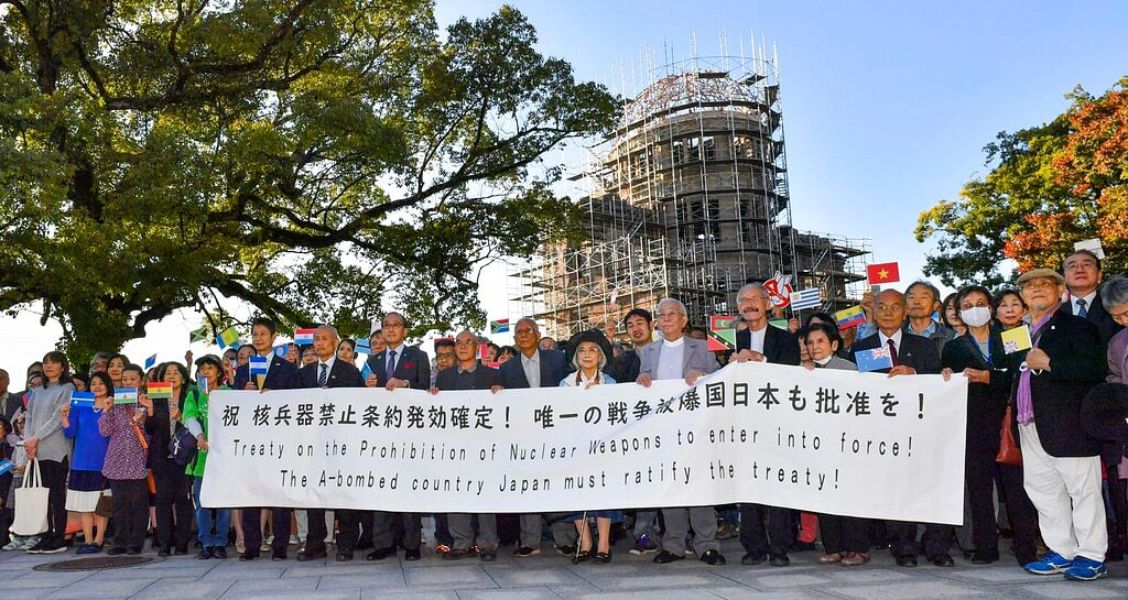 Members of Atomic Bomb survivors groups gather, holding a banner calling for Japanese government to ratify the Treaty on the Prohibition of Nuclear Weapons, with the Atomic Bomb Dome in background, in Hiroshima, western Japan