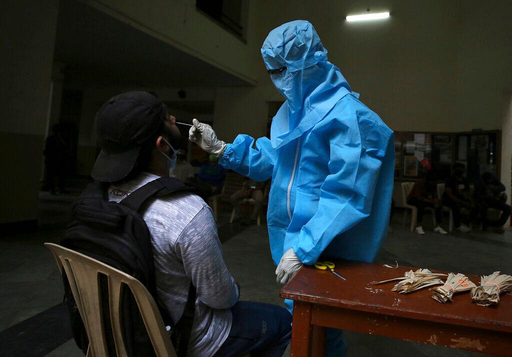 A health worker takes a nasal swab sample
