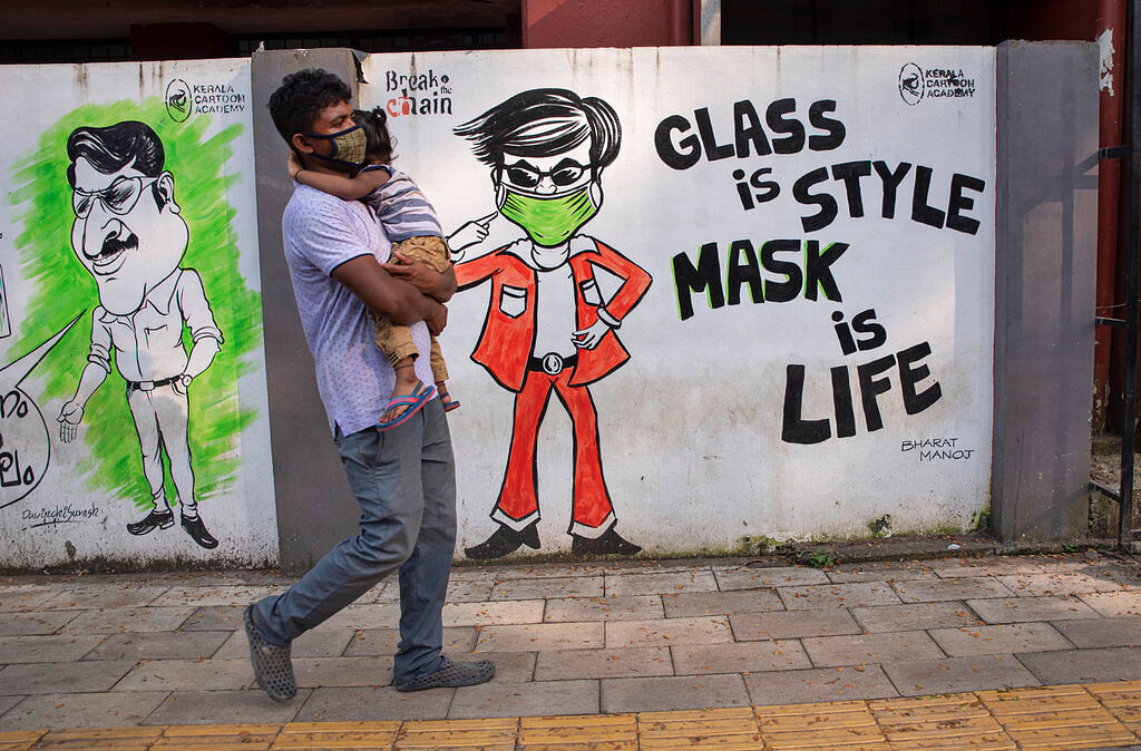 A man wearing a face mask as a precaution against the coronavirus carries a child and walks past a graffiti in Kochi, Kerala