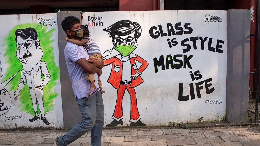 A man walks past graffiti in Kochi, Kerala