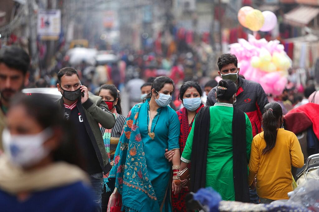 Indians, most of them, wearing face masks as a precautionary measure against the coronavirus crowd a Sunday market in Jammu