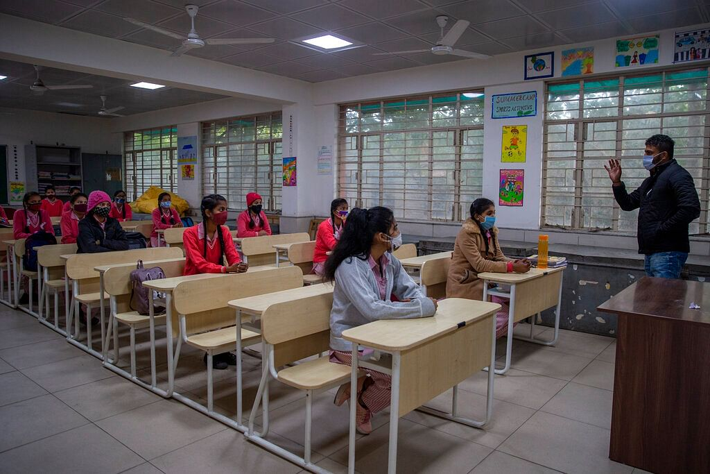 Students wearing face masks as a precaution against the coronavirus, attend classes as schools reopen after being closed for months due to the COVID-19 pandemic in New Delhi, India