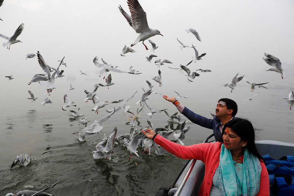 Indian feeds Siberian gulls from a boat on the River Ganges in Varanasi, India.