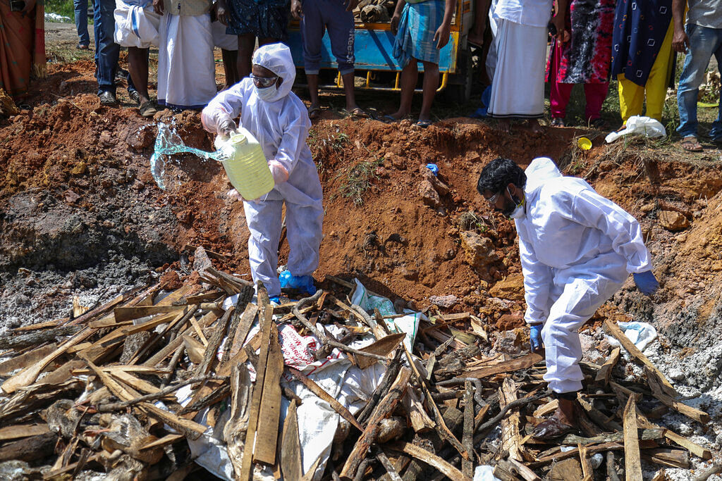 Health workers in protective suits prepare to set fire after culling ducks following the detection of H5N8 strain of bird flu among domestic birds in Alappuzha district, Kerala