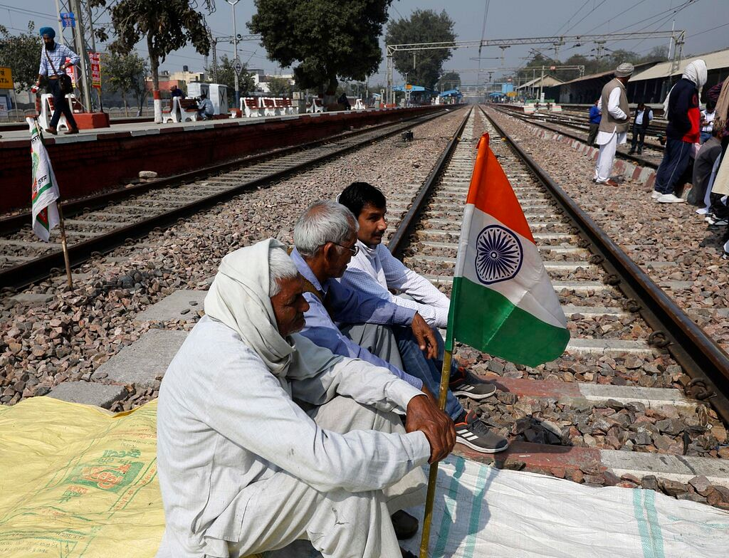 Farmers block a railway track during a protest denouncing three farm laws approved by Parliament in September