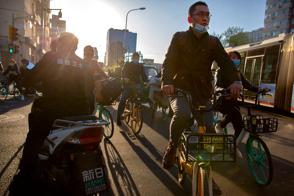 People wearing face masks to prevent the spread of COVID-19 ride bicycles along a street in Beijing
