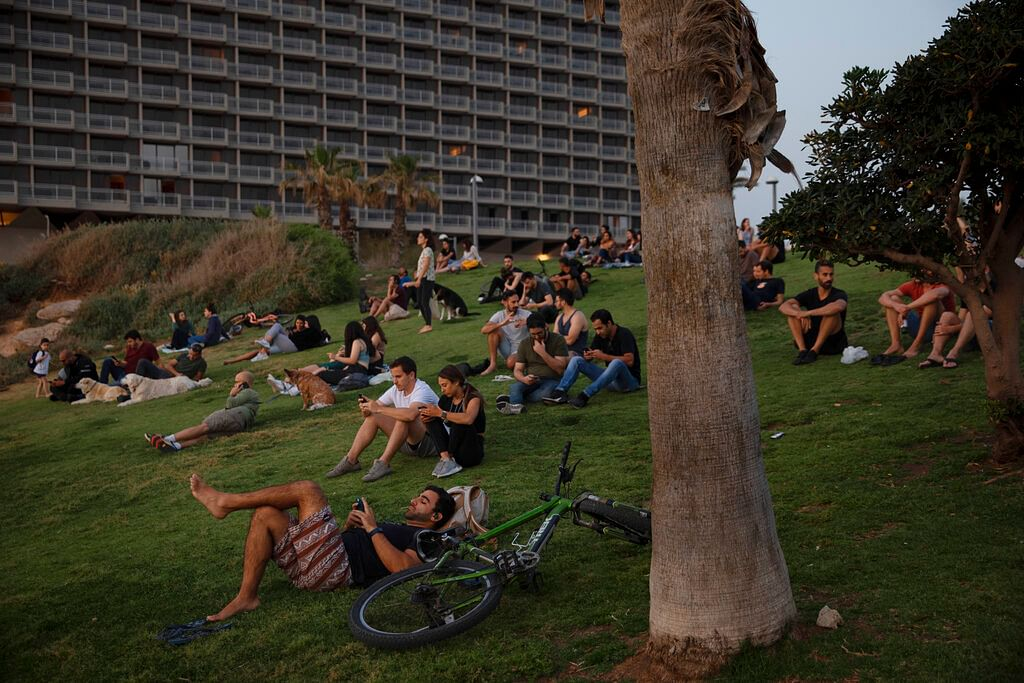 People without face masks watch the sunset, in Tel Aviv, Israel, Sunday, April 18, 2021. mass vaccination drive.