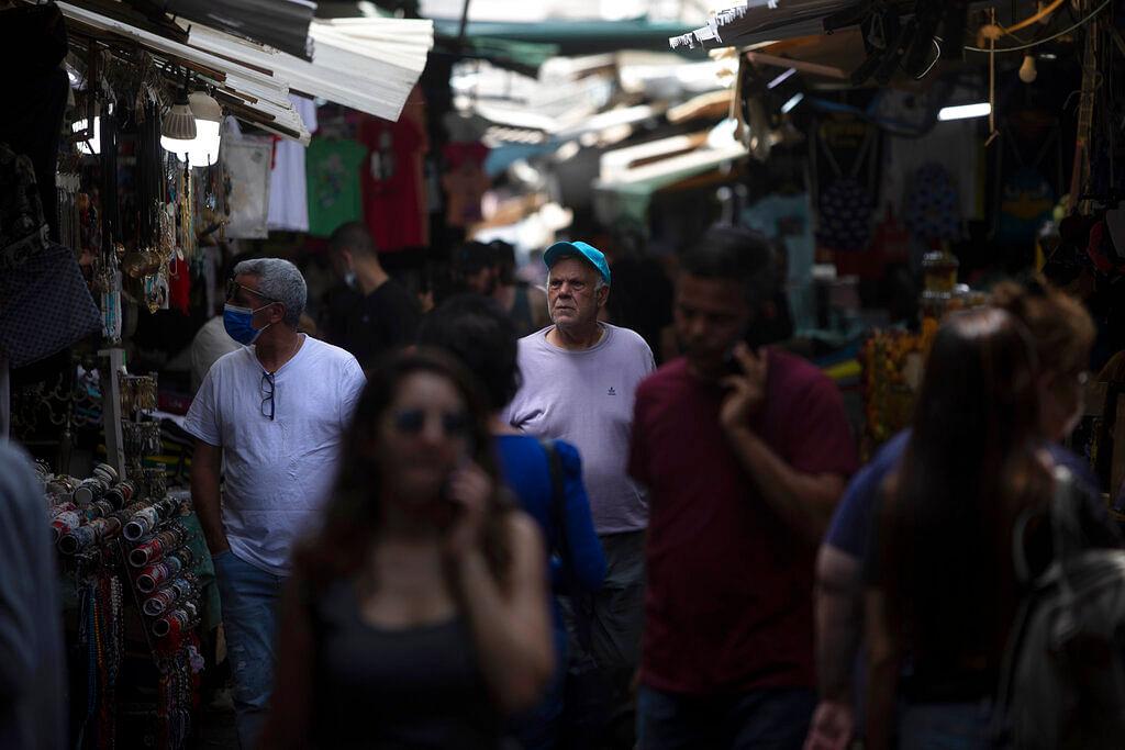 Israelis walk in a market in Tel Aviv, Israel, Sunday, April 18, 2021.