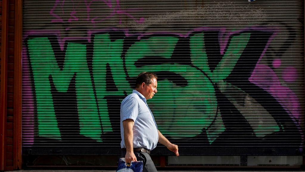"""A man without a face mask walks by a """"mask"""" graffiti"""