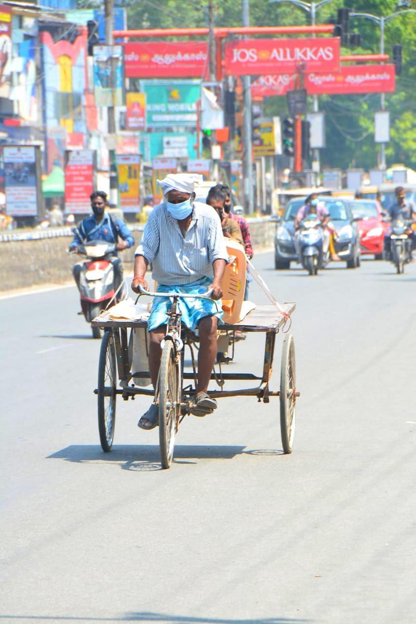 சுட்டெரிக்கும் வெயிலில் சைக்கிள் ரிக்ஷா ஓட்டிச் செல்லும் தொழிலாளி