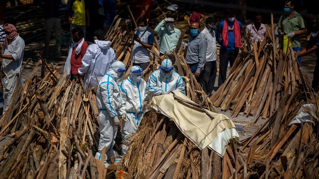 People perform rituals next to a funeral pyre