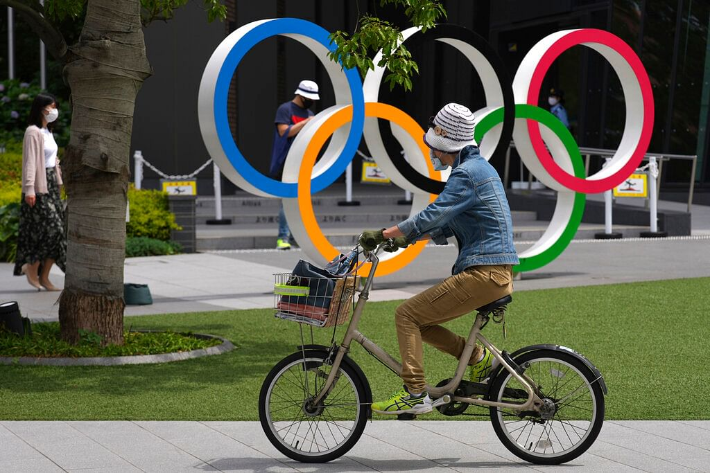 A woman rides a bicycle near the Olympic Rings