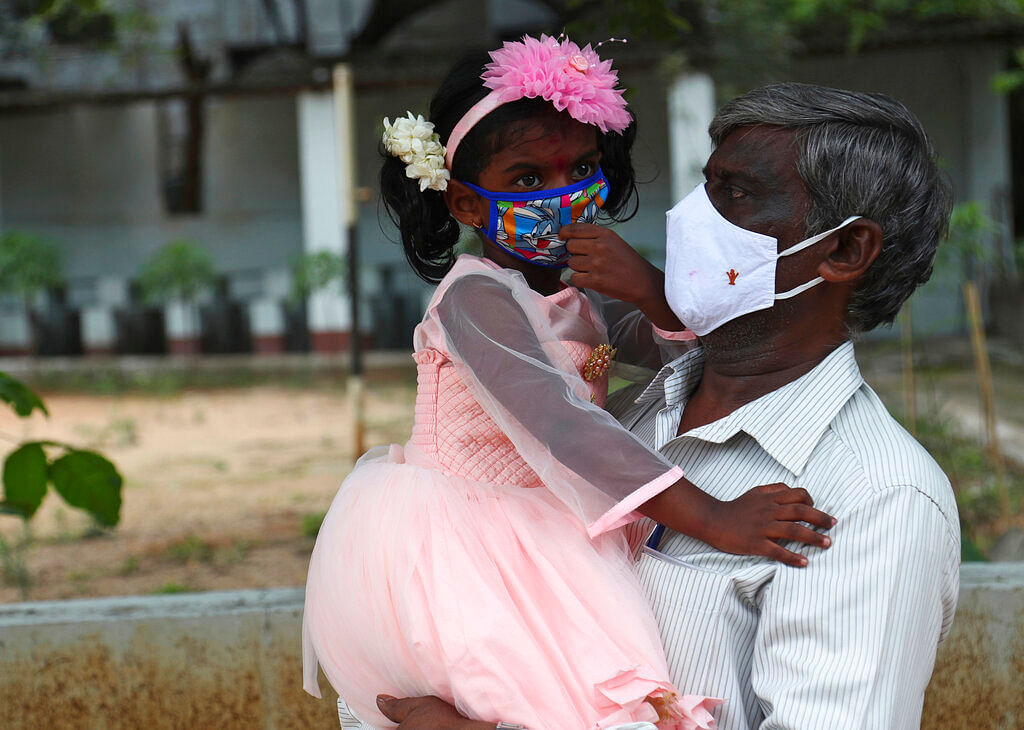 A man carries his granddaughter wearing face masks