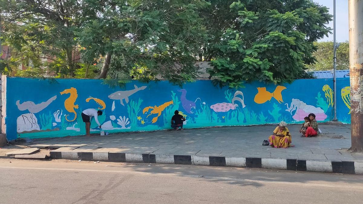 மெரினா அருகே சுவர் ஓவியம் வரையும் இளைஞர்கள்