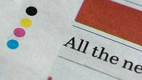 Four Coloured dots printed at the bottom of a newspaper