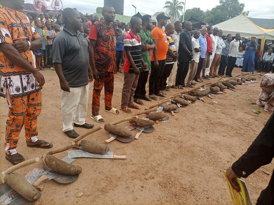 LG boss presenting constituents with tuber of yam, hoe and cutlass