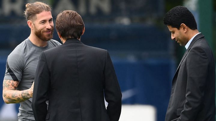 Paris Saint-Germain's Spanish defender Sergio Ramos (L) salutes PSG's Brazilian sporting director Leonardo (C) next to president Nasser Al-Khelaifi as he arrives for a training session at the club's Camp des Loges training ground in Saint-Germain-en-Laye on September 27, 2021 on the eve of their UEFA Champions Leage first round group A football match against Manchester City.