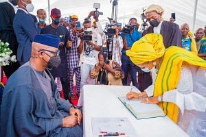 A female council chairmen signs the register as Abiodun looks on