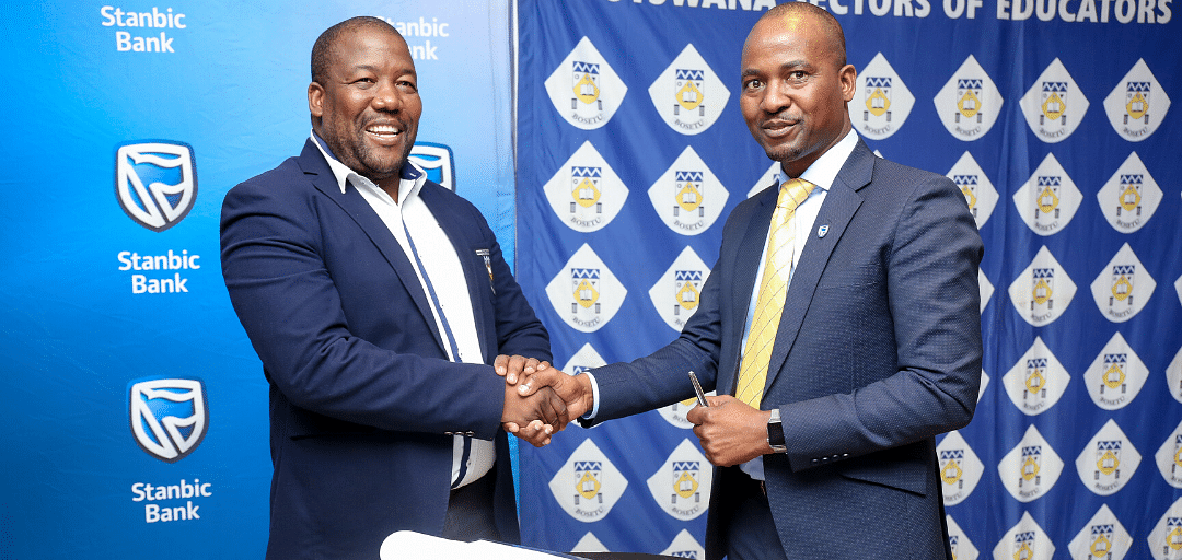 Right to left: Stanbic Bank Botswana CFO, Mr. Chose Modise (acting on behalf of the Chief Executive) and BOSETU President, Mr. Winston Radikolo, shake hands after the contract signing.
