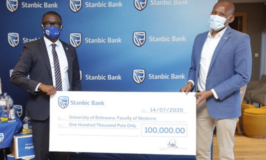 Stanbic Bank Botswana Chief Executive, Mr. Samuel Minta, hands the cheque to Professor Mosepele Mosepele of the Presidential COVID-19 Task Force