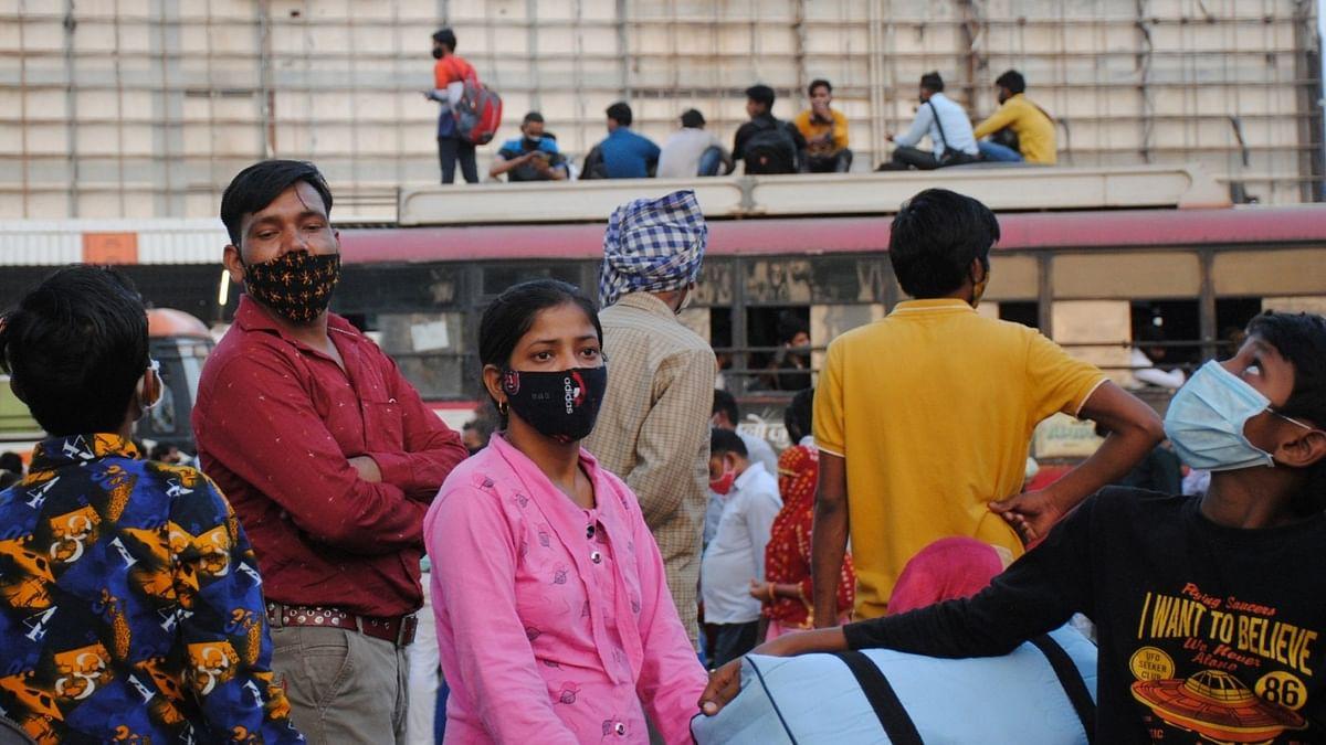 दिल्ली लॉकडाउन: घर जाने के लिए बस स्टैंड पर कतार में खड़े प्रवासी