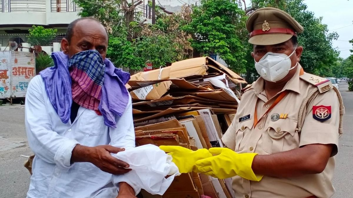 पटरी दुकानदारो और मजदूरो को कोरोना की दवाईयो की किट वितरण करते पुलिस कर्मी
